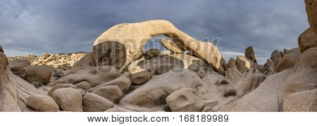 Panorama of famous Arch Rock in Joshua Tree National Park during a cloudy day.