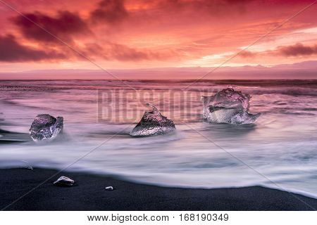An iceberg along the shore of Jokulsarlon glacial lagoon during a vibrant red sunrise rests motionless as it is framed by cold ocean water.