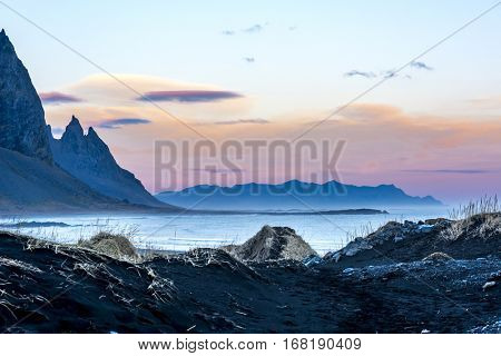 A volcanic sand beach in Iceland framed against jagged mountains and a beautiful pastel sunset as day slips into night.