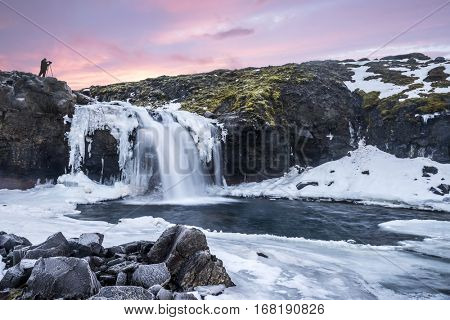 A cold snowy waterfall in the highlands of Iceland framed by pastel skies and rugged terrain offers scenic landscape epitomizing the frozen wilderness.