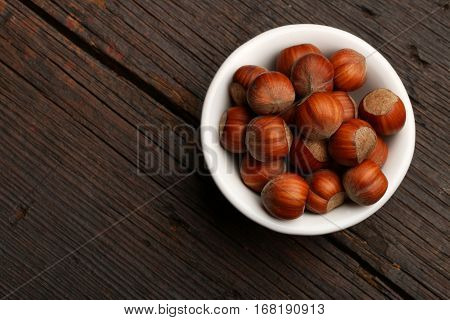 Group of delicious nutshells in a bowl over a wooden background
