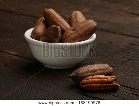 Group of pecan nuts in a bowl over a wooden background