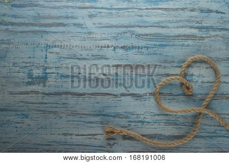 heart of rope lying on a wooden blue background color