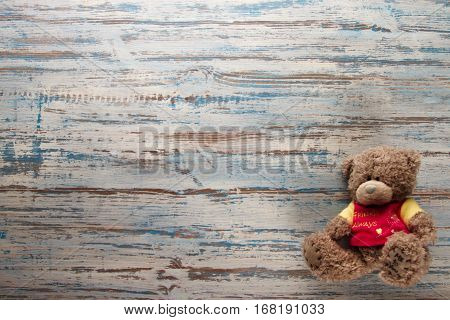 Teddy bear lying on wooden blue background color