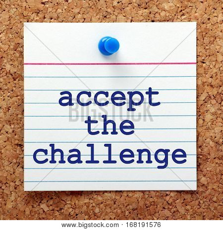 The words accept the challenge in blue text on a note card pinned to a cork notice board as a reminder to embrace change and opportunities