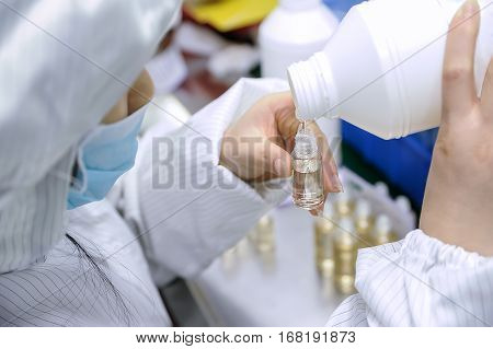 Lab worker filling the bottle with e-liquid solution