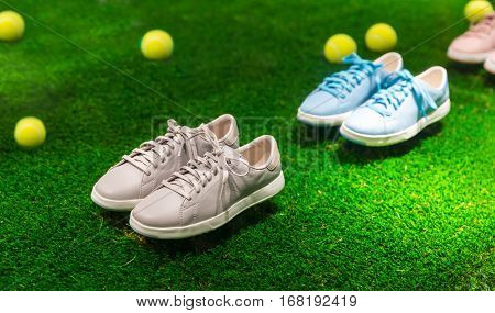 Sport shoes and tennis balls on a grass