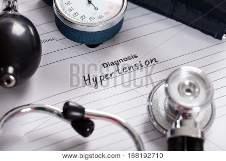 Close-up Of Text Diagnosis Hypertension;Stethoscope And Blood Pressure Gauge On Medical Form
