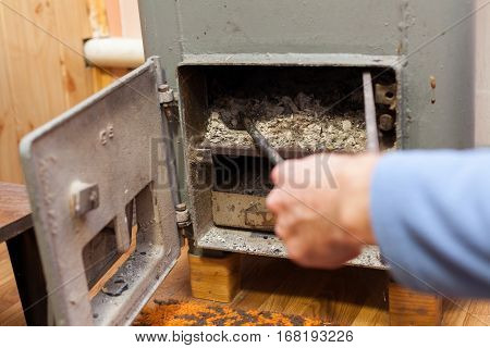 Man clean Burn wood coals of fire in Solid bio fuel boiler