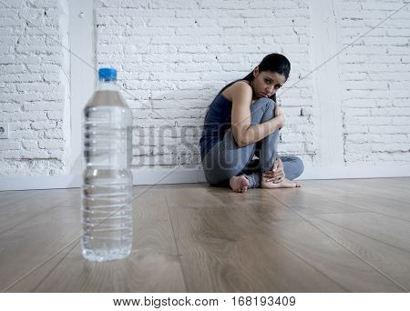 young woman or teenager girl sitting on ground alone and worried at home suffering nutrition and eating disorder in diet and weight loss obsession with bottle of water in anorexia and bulimia concept