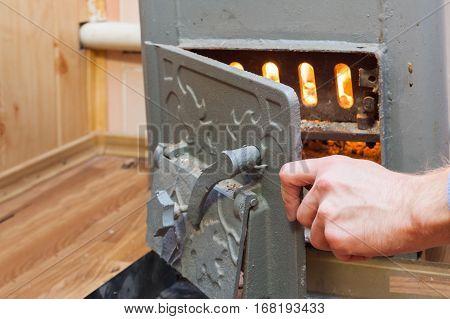 Man close the door in Solid bio fuel boiler