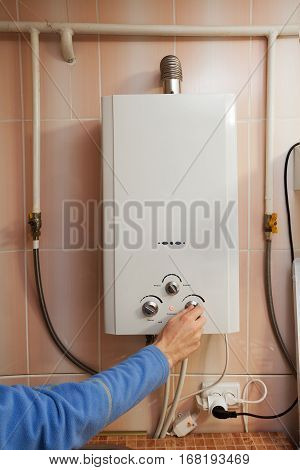 Men hand regulate the temperature of hot water in Gas water heater