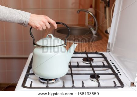 Girl put blue kettle on a kitchen gas stove