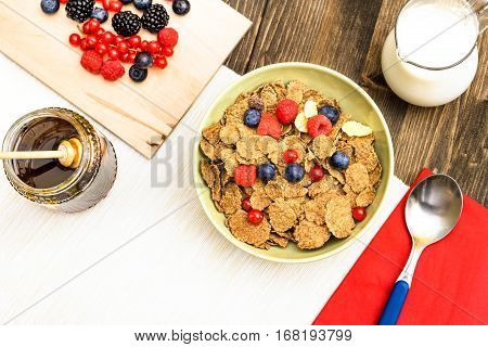 Cereal flakes berries breakfast bowl with milk and honey top view on old wood table - Morning healthy meal concept with wheat bran petals and mixed red fruits - White copy space