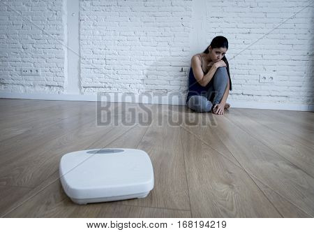 young woman or teenager girl sitting on ground alone and worried at home suffering nutrition and eating disorder in diet and weight loss obsession with scale in anorexia and bulimia concept