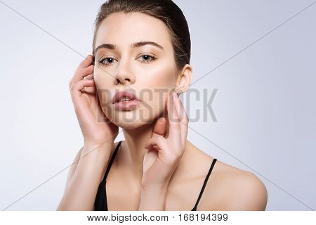 Accentuating face. Magnetic beautiful young woman doing her job in a studio while posing for a photographer and standing isolated on white background
