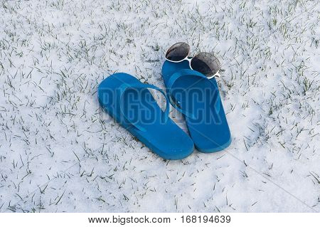 Flip flops with sunglasses on a lawn covered with snow
