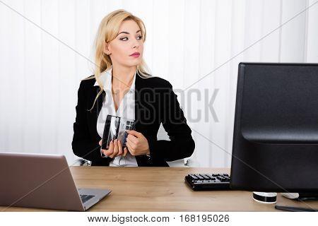 Businesswoman Stealing A Calculator From Office Desk