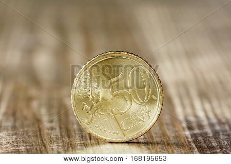 Extremely close up of fifty euro cent on the wooden surface