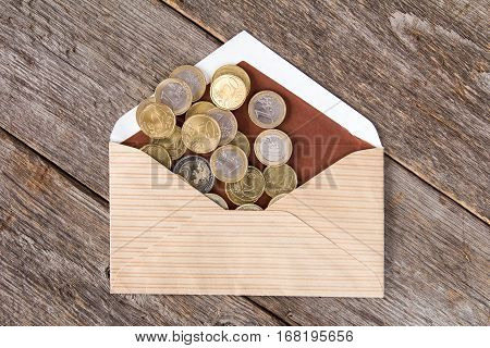 Euro currency coins scatter from open envelope