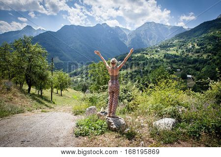 happy woman tourist admiring views of the mountains. beautiful rocks background. Back view.