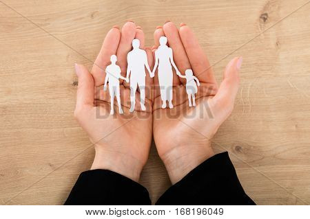 Close-up Of A Woman Hand Holding Family Papercut On Wooden Desk