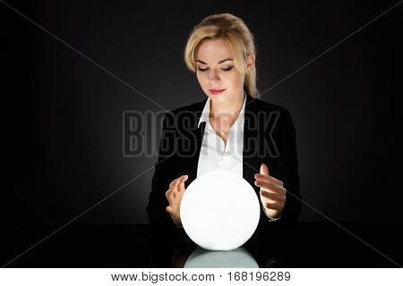 Businesswoman Looking Into The Future In A Crystal Ball On Black Background. Fortune Teller Predicting Future