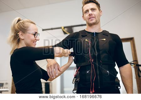 Smiling Woman Putting Ems Suit On Young Man