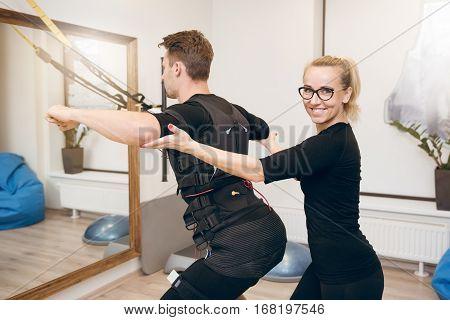 Happy Female Coach Training Man With Ems