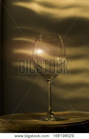 Full view of a red wine glass standing on a traditional wooden shelf in a kitchen at home.