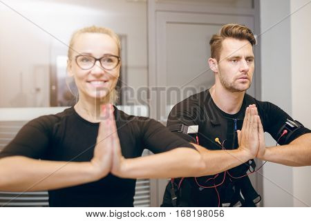 Concentrated Sportsman And Happy Trainer In Yoga Pose