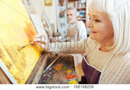 Make art. Female pretty elderly artist spending time in painting class and enjoying her hobby while working.