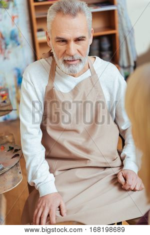 Serious painter. Concentrated professional elderly artist wearing uniform and sitting in painting class while working.