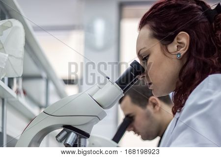 Female And Male Medical Or Scientific Researchers Or Women And Men Doctors Looking Through A Microsc