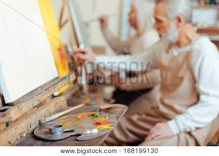 Live for art. Male happy concentrated artist painting a picture while spending time in painting class and working.