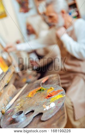 Work for art. Male talented concentrated artist drawing a picture while spending time in painting class and working.