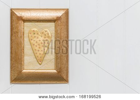 One Gold Heart. White Wood Background. Copy Space.