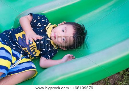 Little Asian Kid Playing Slide At The Playground.