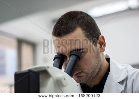 Female Medical Or Scientific Researcher Man Doctor Looking Through A Microscope In A Laboratory. You