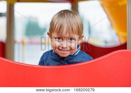 boy hiding from the rain on the playground. Shy child running around the playground.