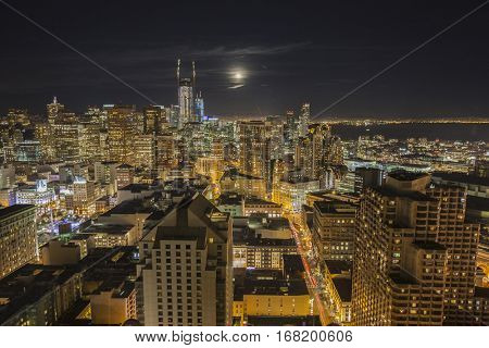 San Francisco, California, USA - January 13, 2017:  Night cityscape skyline view with moon rising over San Francisco Bay.