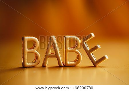 Single word 'Babe' in gold lettering. Gold letters spelling BABE. Letters forming word BABE written against golden background.