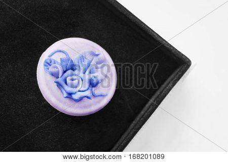 Vintage blue ceramic brooch in black jewel box closeup