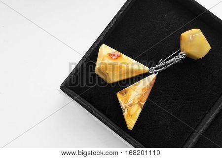 Amber brooch in black jewel box closeup