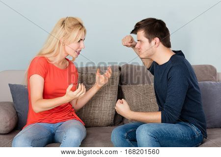 Young Frustrated Infidelity Couple Sitting On Couch Having Argument With Each Other At Home