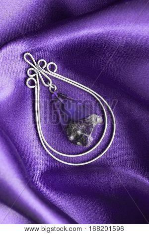 Vintage amethyst trinket on purple crumpled satin