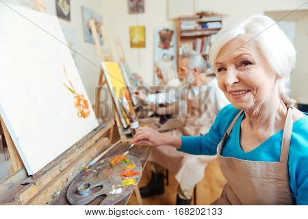 Having good time. Female elderly delighted artist smiling and painting picture while working in painting studio. poster