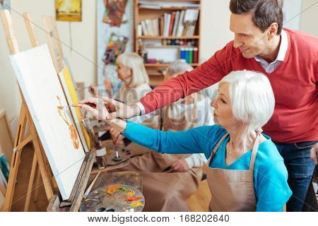 Give an advice. Delighted professional artist helping elderly woman while spending time in painting studio and drawing a picture. poster