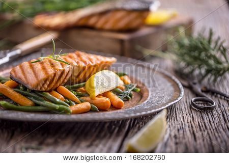 Salmon fillets. Grilled salmon sesame seeds herb decoration on vintage pan or black slate board. fish roasted on an old wooden table.Studio shot.