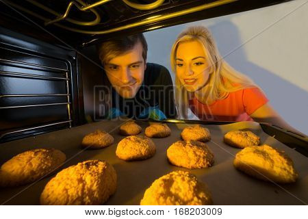 Close-up Of Young Couple Baking Cookies In The Oven